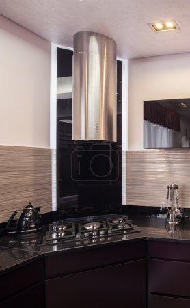Dark kitchen with chromed hood