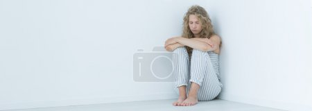 Photo for Young woman sitting alone and barefoot in a bright room corner - Royalty Free Image