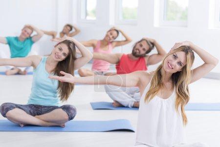 Photo pour Jeunes hommes et femmes faisant ensemble un cours de pilates - image libre de droit