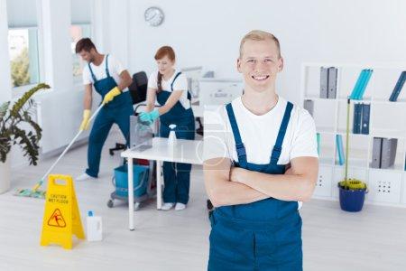 Photo pour Nettoyant professionnel heureux et deux travailleurs nettoyage bureau - image libre de droit