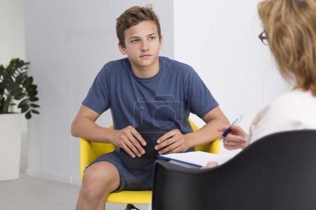 Photo pour Adolescent garçon en thérapie session avec femme psychologue - image libre de droit