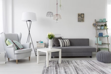 Photo for Shot of a modern living room interior with a classic grey armchair - Royalty Free Image