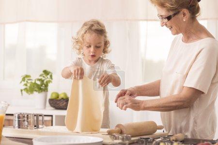 Photo pour Intérieur de cuisine lumineuse avec enfant faire le gâteau avec ses sourit grand-mère - image libre de droit