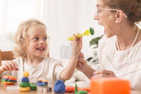 Photo pour Sourit fille jouant dans la cuisine avec sa grand-mère de pâte à modeler - image libre de droit