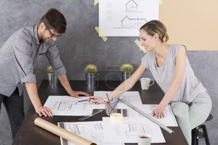 Man and woman in office with documents and drawings