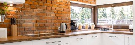 Photo pour Coin cuisine moderne avec un mur de briques élégant et une grande fenêtre horizontale - image libre de droit