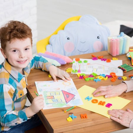 Photo for Boy drawing a home during occupational therapy - Royalty Free Image