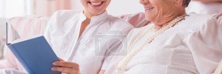 Photo for Yong carer reading a book to a senior woman, panorama - Royalty Free Image