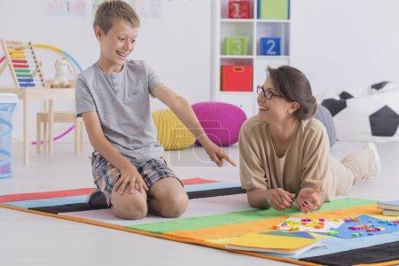 Photo pour Baby-sitter professionnel souriant et heureux écolier jouant ensemble - image libre de droit