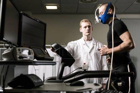 Doctor monitoring man on treadmill