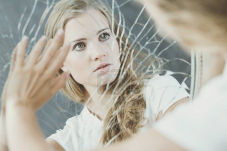 Photo for Teenage girl with personality disorder touching broken mirror - Royalty Free Image