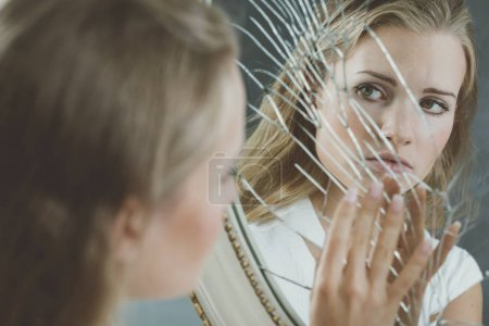 Photo for Beautiful woman with mental disorder touching broken mirror - Royalty Free Image
