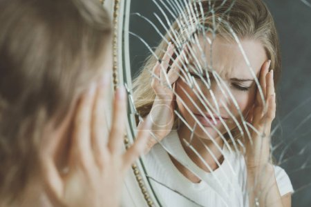 Photo for Reflection of girl with bipolar disorder in broken mirror - Royalty Free Image