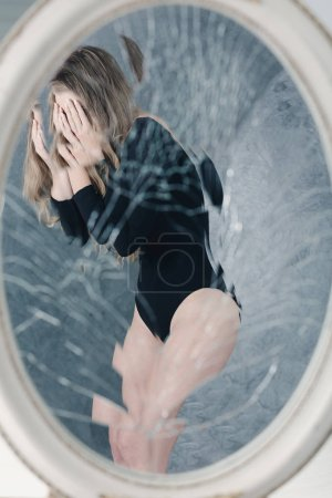 Photo for Reflection of anorexic girl in a round broken mirror - Royalty Free Image