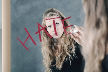 "Photo for Girl with mental disorder writing word ""hate"" on mirror - Royalty Free Image"
