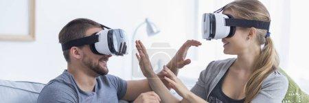 Photo pour Joyeux jeune couple portant des lunettes de réalité virtuelle à l'intérieur - image libre de droit
