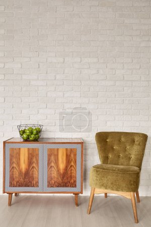Photo for Interior with white brick wall, wood dresser and green chair - Royalty Free Image