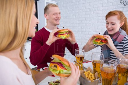 Man and women eating burgers