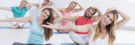 Happy people stretching on mats