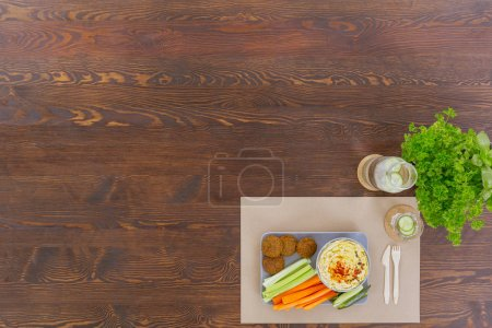 Photo for Vegetarian meal with hummus and falafel lying on wood table - Royalty Free Image