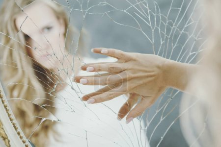 Photo for Teenage girl with depression holding her hand on the broken mirror - Royalty Free Image