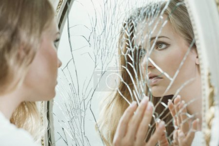 Photo for Young pretty girl with teenage problems looking in the broken mirror - Royalty Free Image