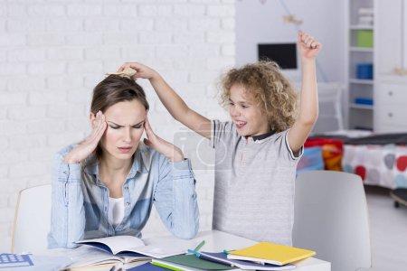 Photo pour Enfant, gênant sa mère fatiguée avec des maux de tête - image libre de droit