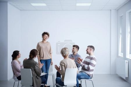 Photo pour Femme heureuse parlant devant le groupe pendant la psychothérapie - image libre de droit