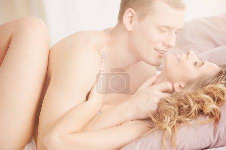 Photo pour Beau jeune amant caressant le corps de la femme dans la chambre lumineuse - image libre de droit