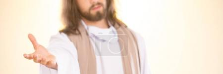 Photo for Jesus Christ reaching out his hand against bright background - Royalty Free Image