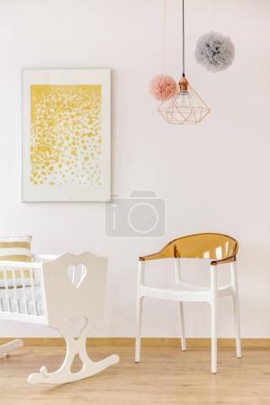 Photo pour Pépinière décor doré avec poster sur berceau et chaise - image libre de droit