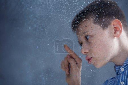 Boy looking at raindrops