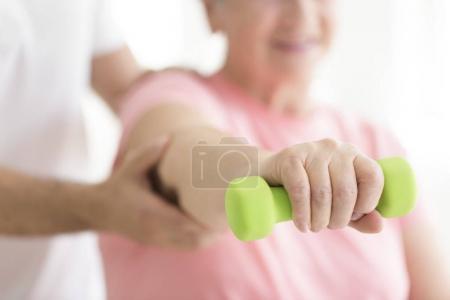 Elderly patient holding minor dumb-bell