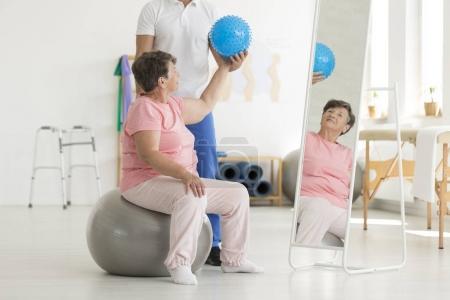 Photo pour Ensemble d'exercices d'équilibre isométrique, y compris une boule bleue pointue tenue par la patiente âgée alors qu'elle est assise sur une boule grise devant un miroir - image libre de droit