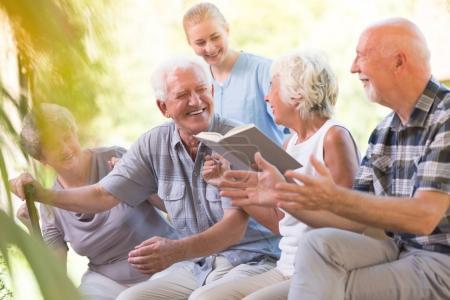 Photo pour Heureux aînés de maison de soins infirmiers passer la journée à l'extérieur et lire le livre ensemble - image libre de droit