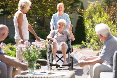 Happy grandma in wheelchair waving to her friend w...