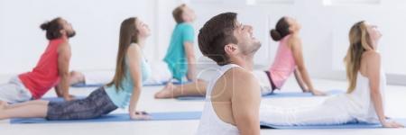 Photo pour Les participants aux cours et instructeur de yoga reposent sur des nattes et se penchent vers l'arrière - image libre de droit