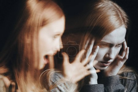 Photo for Girl with schizophrenia covering her ears to not hear the voice of her alter ego. Blurred person - Royalty Free Image