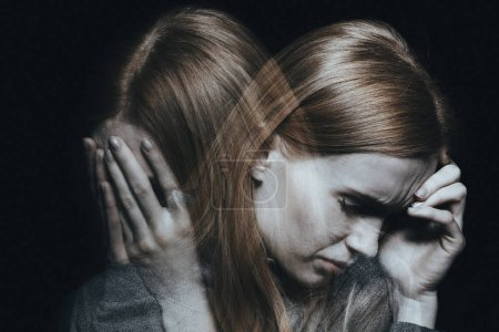 Photo for Young red haired female with mood disorder crying and having a headache - Royalty Free Image