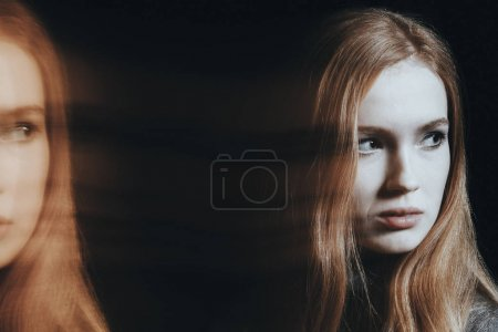Photo for Suffering girl with psychosis and split personality. Photo of blurred and multiple faces against black background - Royalty Free Image