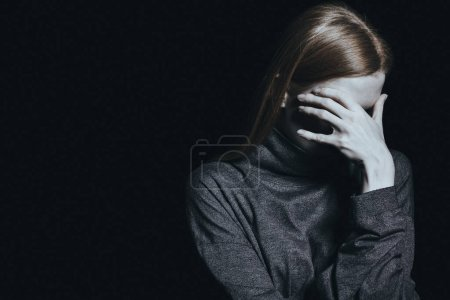 Photo for Desperate woman with phobia and anxiety against black background with copy space - Royalty Free Image