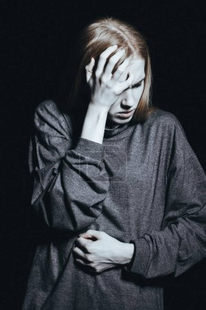 Photo for Young woman with pain of existence touching her head and stomach - Royalty Free Image