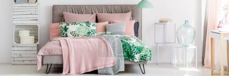 Photo for Glass containers on white stools next to king-size bed with pink blanket in pastel cozy bedroom interior - Royalty Free Image