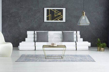 Photo for Modern poster above designer sofa with grey pillows in spacious living room with gold table on carpet - Royalty Free Image