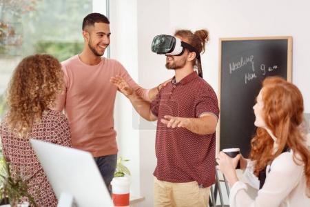 Photo pour Homme avec lunettes de réalité virtuelle tester un nouveau produit lors d'une réunion d'équipe au bureau - image libre de droit
