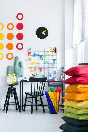 Photo pour Gros plan de pile d'oreillers arc-en-ciel et bureau noir avec chaise en bois dans une pièce colorée pour un élève - image libre de droit