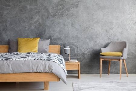 Photo pour Chaise et lampe grises sur table de chevet en bois dans une chambre sombre avec mur en béton et oreiller jaune sur le lit - image libre de droit