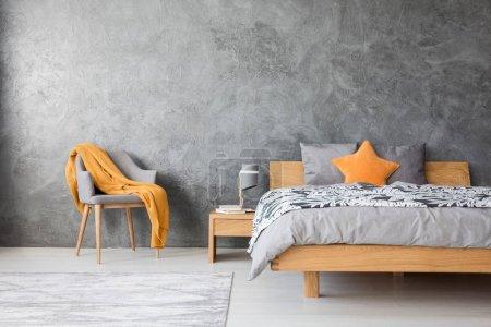 Photo pour Oreiller étoile orange sur lit en bois contre mur en béton avec espace de copie dans la chambre grise avec chaise - image libre de droit