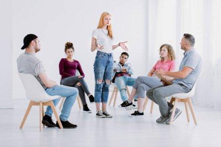 Photo pour Fille problématique debout à l'intérieur d'un cercle pendant la thérapie de groupe avec des adolescents rebelles - image libre de droit