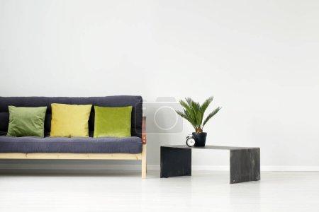 Photo pour Plante et horloge sur table en métal à côté d'un canapé noir avec oreiller vert et jaune à l'intérieur plat avec mur vide - image libre de droit